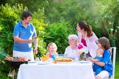 Grote jonge familie die vlees voor lunch roosteren stock fotografie