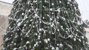 Grote Kerstboom met zilveren speelgoed en lichten in het zware sneeuwstormsneeuw vallen stock footage