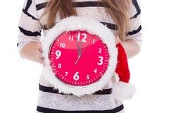 Grote klokken een Kerstmishoed in vrouwelijke handen Nieuw jaar 12 uren Royalty-vrije Stock Afbeelding