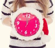 Grote klokken een Kerstmishoed in vrouwelijke handen Nieuw jaar 12 uren toning Stock Foto's