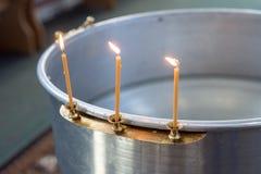 Grote kom water voor het doopsel van een baby met kaarsen orthodoxy Griekse Katholieken drie kaarsenbrandwond aan de kant royalty-vrije stock afbeelding