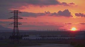 Grote krachtcentrale met reusachtige elektrische pylonen en ongelooflijke zonsondergang stock videobeelden