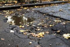 Grote kuil met stenen op de asfaltweg stock fotografie
