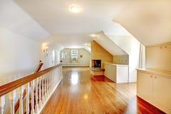 Grote lange zolderruimte met open haard. Leeg met gouden hardhout. royalty-vrije stock afbeeldingen