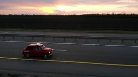 Grote luchtlengte van rode kleine retro autoaandrijving op 4 steegautosnelweg in zonsondergang of zonsopgang met gedraaide koplam stock footage