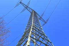 Grote machtspyloon die elektriciteit op een plattelandsgebied vervoeren stock fotografie