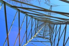 Grote machtspyloon die elektriciteit op een plattelandsgebied vervoeren stock afbeelding