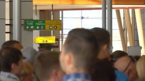 Grote menigte van anonieme vage mensen bij het bureau van de luchthavencontrole stock footage