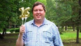 Grote mens die gouden ballons houden die 16 aantal openlucht maken de 16de partij van de verjaardagsviering stock footage