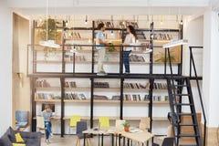 Grote moderne bibliotheek met minimalistic ontwerp, computers, comfortabele zittingen, eerste verdieping met boekenrekken Ochtend royalty-vrije stock foto's