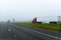 Grote moderne rode semi vrachtwagenaanhangwagen die op uitgangs multilijnen hoog gaan Stock Fotografie