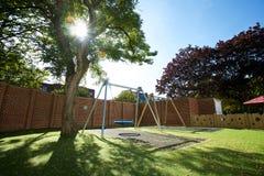 Grote moderne schommeling in een ommuurde tuin met een grote boom in de zonneschijn stock afbeeldingen