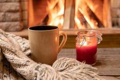 Grote mok met hete thee, en een kaars, wolsjaal, dichtbij comfortabele open haard, hygge, huis zoet huis royalty-vrije stock fotografie