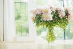 Grote mooie bleek - roze pioenenboeket in glasvaas over vensterachtergrond Lichte Huisdecoratie met bloemen en vaas royalty-vrije stock foto's