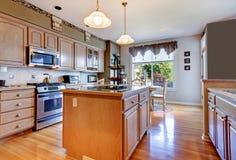 Grote mooie witte keuken met hardhoutvloer en groene muren. Stock Foto's