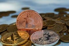 Grote muntstukken bitcoin op een stapel van kleine gele muntstukken Stock Foto