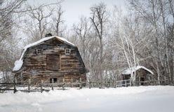 Grote oude bruine houten die schuurzitting achter een omheining van houten posten wordt gemaakt Stock Foto's