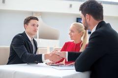 Grote overeenkomst Twee succesvolle en gemotiveerde zakenlieden zitten Stock Afbeeldingen