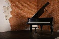 Grote piano met opgeheven deksel dichtbij bakstenen muur royalty-vrije stock afbeelding