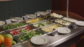 Grote platen met salades en voorgerechten op een buffet stock video