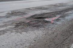 Grote pothole op de weg stock foto's