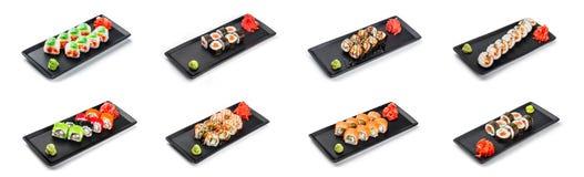 Grote reeks van Sushibroodje - Maki Sushi op zwarte die plaat over witte achtergrond wordt geïsoleerd royalty-vrije stock afbeeldingen