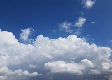 Grote reusachtige witte wolken die zich over blauwe hemel vormen Stock Fotografie