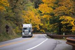 Grote Rig Semi-vrachtwagenaanhangwagen op het winden de weg gele herfst Royalty-vrije Stock Foto's