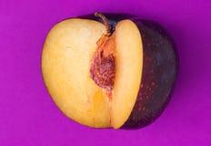 Grote rijpe organische purpere pruim met verwijderd segment op ultraviolette achtergrond Gele dichte omhooggaand van de vleeskuil royalty-vrije stock fotografie