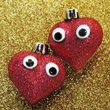 Grote rode harten in liefde met ogen in gouden glitte als achtergrond Royalty-vrije Stock Afbeeldingen