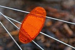 Grote rode plastic reflector op grijs metaalwiel spokes stock foto's