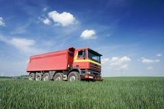 Grote rode vrachtwagen op gebied Stock Foto's