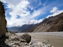 Grote rots naast van de modderrivier in de bergvallei, Royalty-vrije Stock Foto's