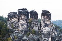 Grote rotsbergen in groen bos in de zomerdag stock afbeeldingen