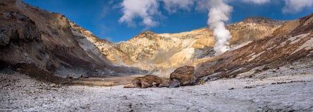 Grote rotsen op de eeuwige sneeuw binnen Mutnovsky-vulkaankrater Stock Afbeeldingen