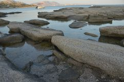 Grote rotsen op de oceaan in het water stock afbeelding