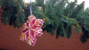 Grote roze sneeuwvlok met kleurrijke lovertjes die op slinger hangen die huis verfraaien stock video