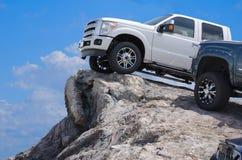 Grote ruwe vrachtwagens op een rotsachtige richel royalty-vrije stock afbeelding