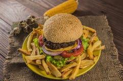 Grote sandwich - hamburgerhamburger met rundvlees, kaas, tomaat Op een houten rustieke achtergrond Close-up Royalty-vrije Stock Foto