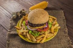 Grote sandwich - hamburgerhamburger met rundvlees, kaas, tomaat Op een houten rustieke achtergrond Close-up Stock Foto