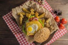 Grote sandwich - hamburgerhamburger met rundvlees, kaas, tomaat Op een houten rustieke achtergrond Hoogste mening Close-up Royalty-vrije Stock Foto's