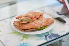 Grote sandwich met vlees en greens op een witte plaat Stock Afbeeldingen