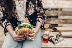 grote sappige hamburger ter beschikking modieuze hipstervrouw die yummy CH houden royalty-vrije stock afbeelding