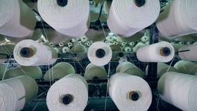 Grote spoelen met wit garen dat terwijl de textielfabrieksmachines werken roteert stock footage