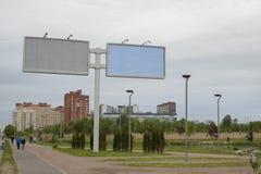 Grote stadsaanplakborden op de achtergrond van de stad en de bewolkte, sombere Noordelijke hemel stock foto's