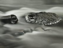 Grote steen met kleine ijskegels in koud melkachtig vaag water van bergstroom. stock afbeelding