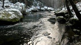 Grote steen met kleine ijskegels in koud melkachtig vaag water van bergstroom. stock video