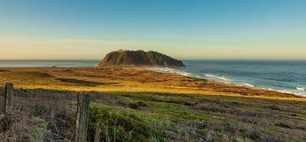 Grote sur lichte post in de afstand met ochtendzonsopgang op gebied en oceaangolven stock afbeelding