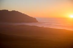 Grote Sur-zonsondergang met vuurtoren op rotsen Stock Afbeelding