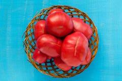 Grote tomaten in een houten mand op een blauwe achtergrond De achtergrond van tomaten Royalty-vrije Stock Foto's